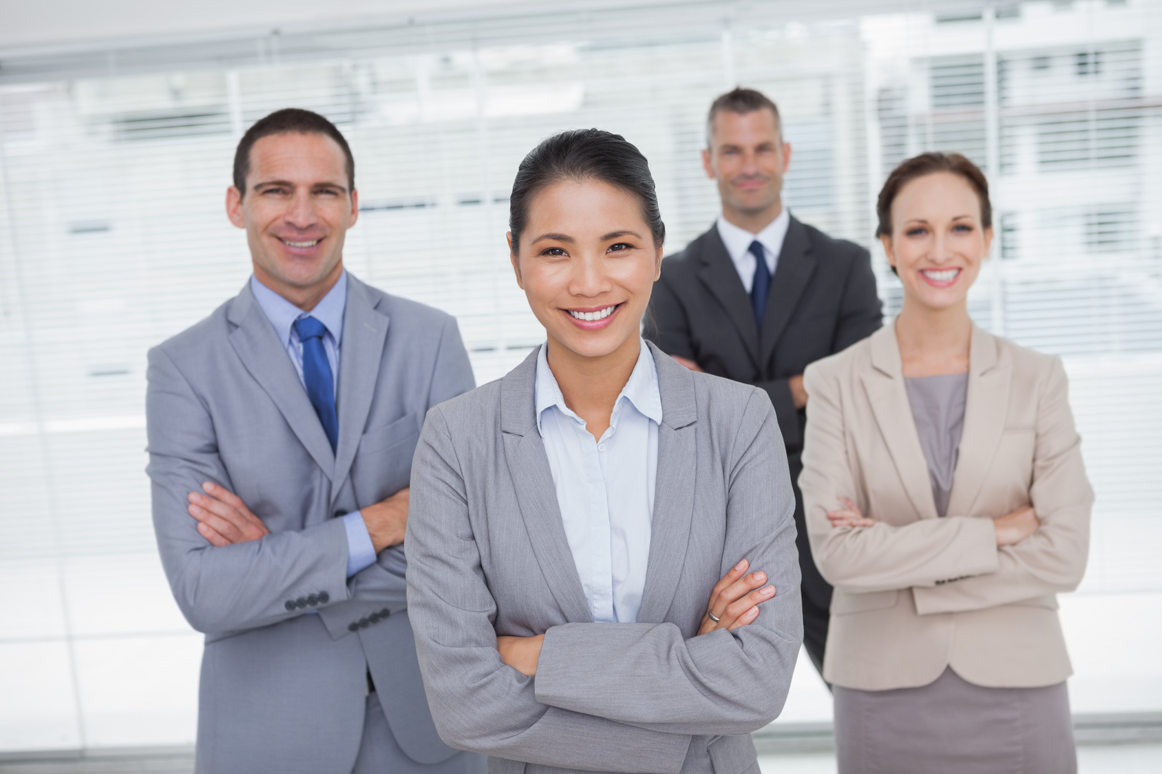 Cheerful work team posing crossing arms in bright office